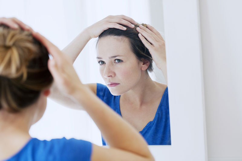 woman-reflecting-about-hair-loss-in-a-mirror