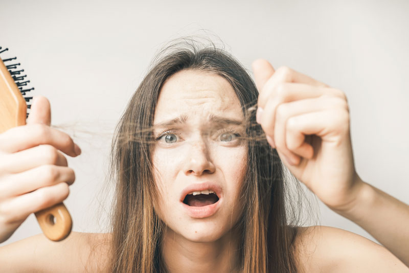 woman-disgusted-with-large-amount-of-hair-loss